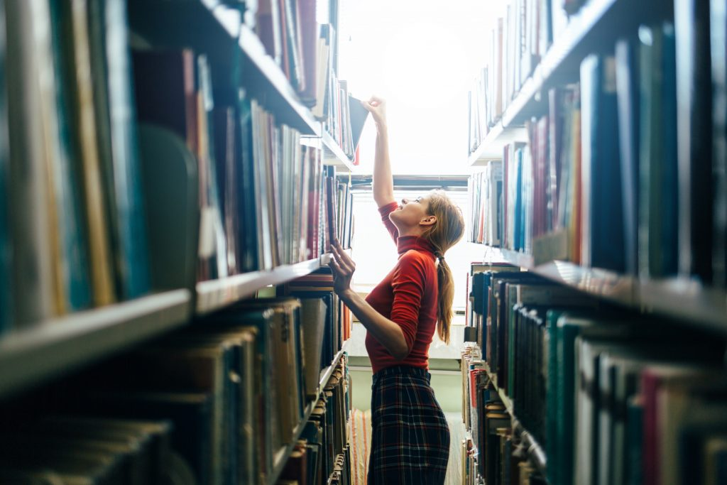 The Tutor Team - Online Tutoring for UK & Asia - Girl reaching for a book in Library